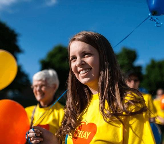 Femme portant un t-shirt du Relais pour la vie, souriant et tenant un ballon.