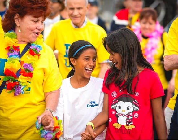 Deux petites filles se tenant la main en souriant, dont une tient aussi la main d'une femme portant un t-shirt du Relais pour la vie.