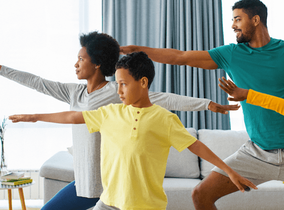 a family of four stand in their living room doing yoga together