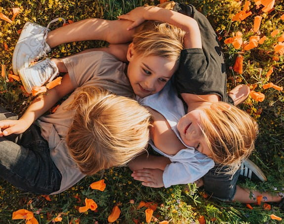 Three young boys are playing together on a grassy field