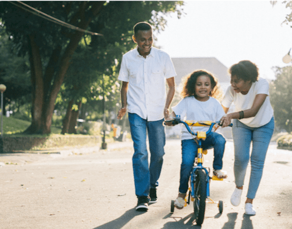 A young girl learning to ride her bike, parents helping her