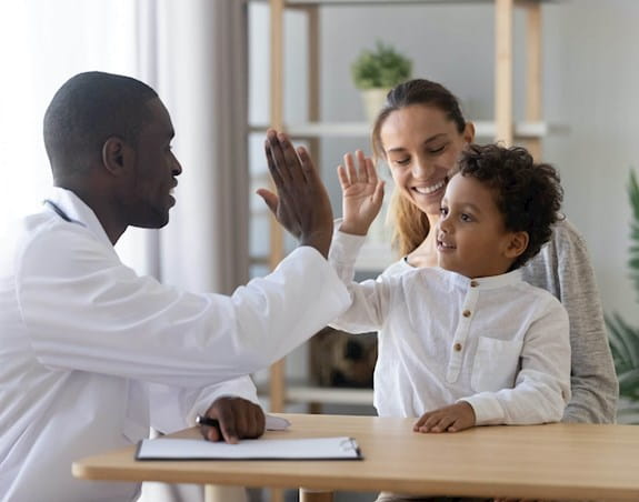Doctor high-fiving a young boy, woman smiling in the background