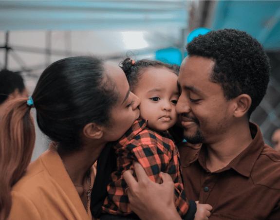 Mère et père enlaçant et embrassant leur fille sur les joues.