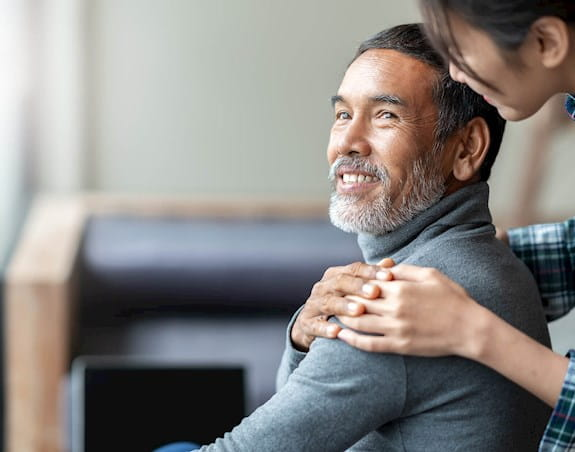 A man is looking back and smiling at a woman who has her hand on his shoulder