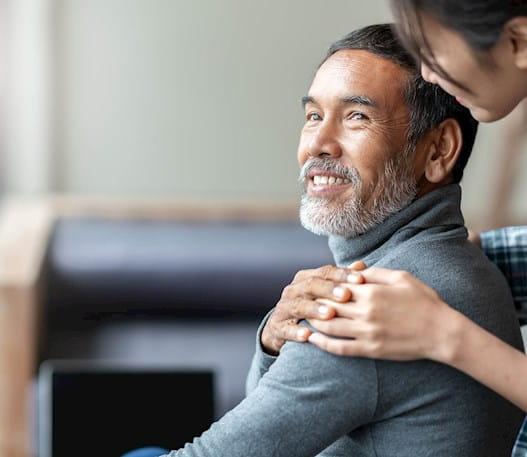 Older man looking sideways, smiling, someone resting hand on his shoulder