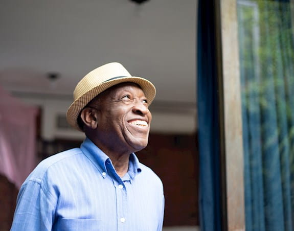 Man wearing a hat and blue shirt looking up and smiline
