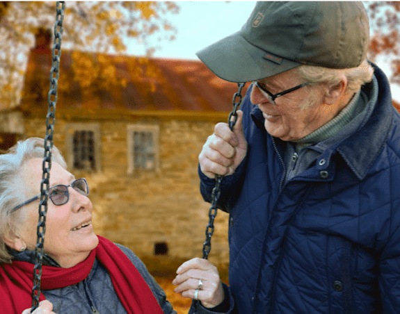 An elderly man and woman are smiling at each other while the woman sits on a swing
