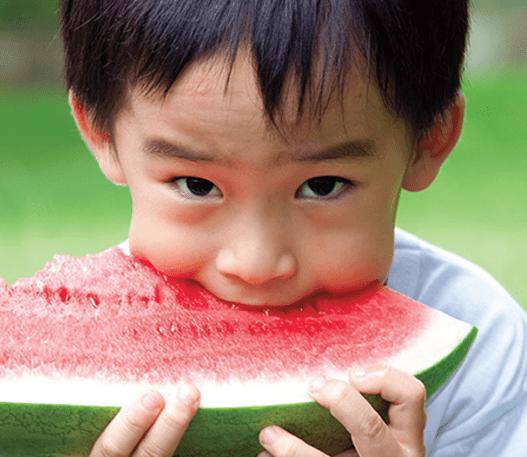 Un enfant prenant une bouchée de pastèque
