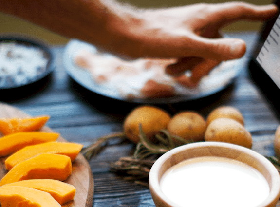 A hand is swiping through a recipe on a tablet that is on a table full of food