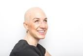 A close up of a bald woman