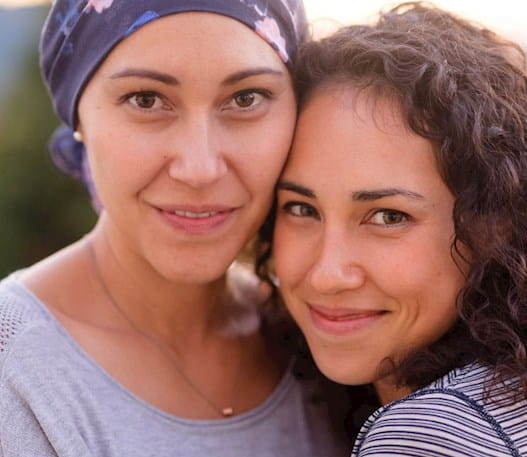 A smiling woman with cancer wearing a scarf on her head with another woman.