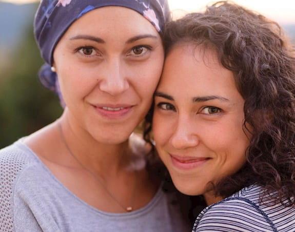 Une femme atteinte de cancer, un foulard sur la tête, qui sourit, en compagnie d'une autre femme.