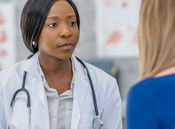 A female doctor wearing a lab coat and stethoscope addressing a patient.