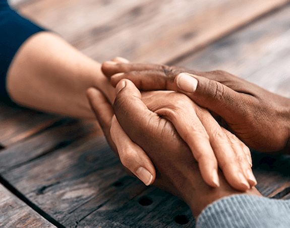 An individuals hand is being embraced by the hands of another person