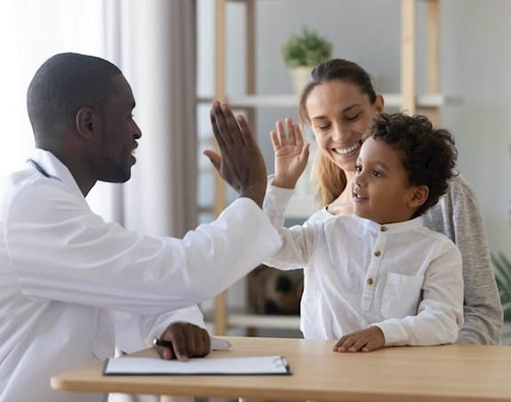 A young boy sitting with his mother and high-fiving his doctor.