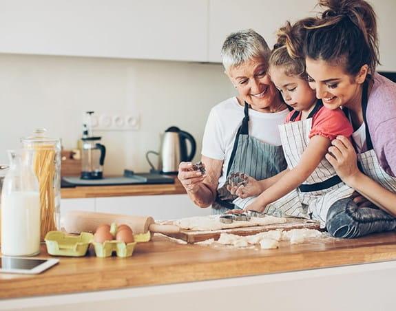 Une grand-maman, sa fille et sa petite-fille en train de cuisiner dans la cuisine.
