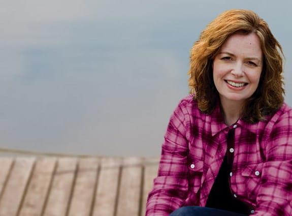Une femme souriant qui porte un chemisier rose.