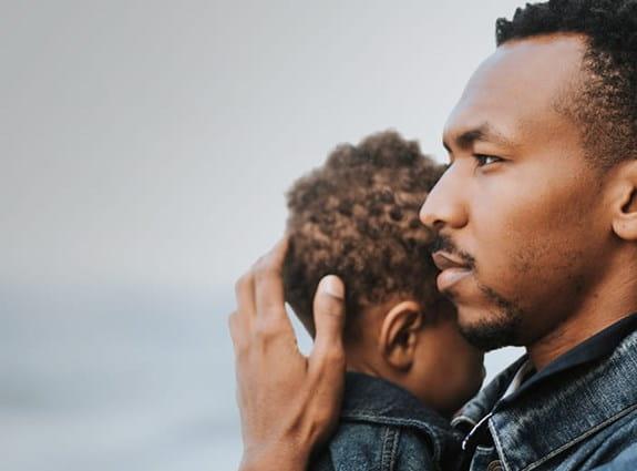 Un homme regardant au loin en tenant la tête de son jeune fils près de lui.