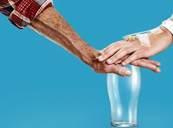 Two people placing their hands on an empty alcohol glass.