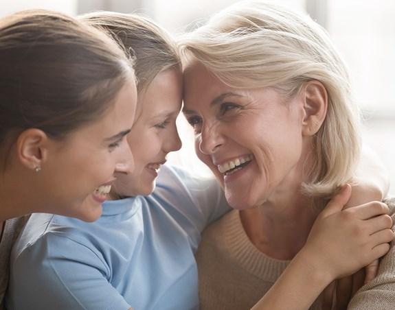 Une fillette souriant en compagnie de sa mère et de sa grand-mère.