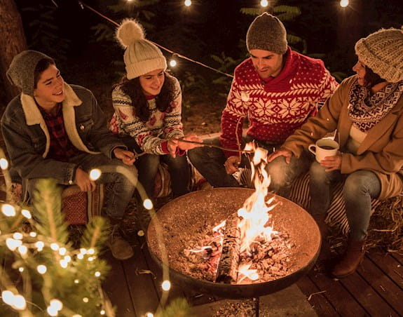 A group of people sitting around a campfire, some sipping hot chocolate and roasting marshmallows.
