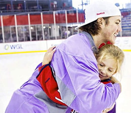 A hockey player hugs a young fan.