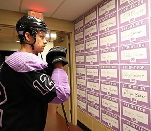 Un joueur de hockey regardant des cartes avec les mots « I fight for » suivis du nom d'une personne.