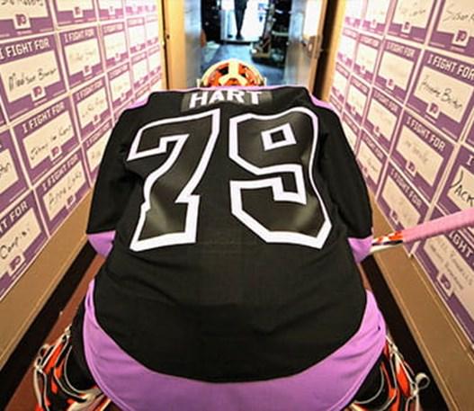 Un joueur de hockey assis, vu de dos, portant le chandail numéro « 79 » au nom de « HART ».