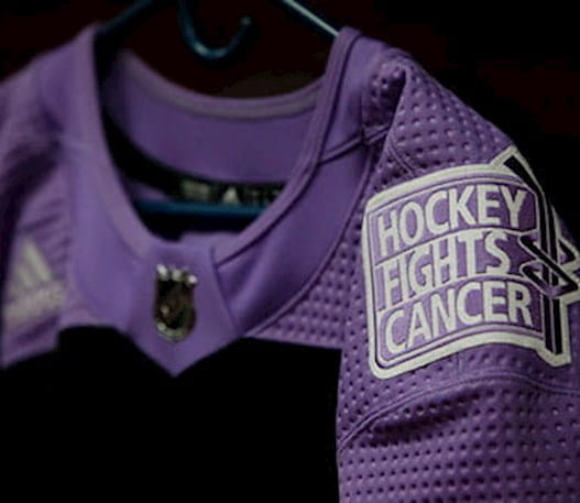 La photo d'un chandail lilas avec l'écusson de Hockey Fights Cancer.