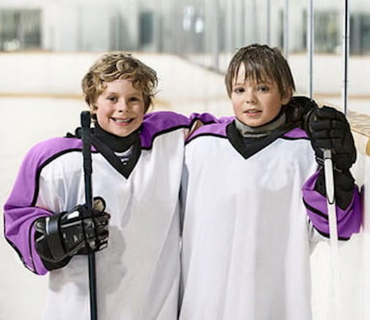 2 young hockey players smiling on the ice.