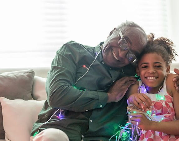A grandfather and his granddaughter smiling