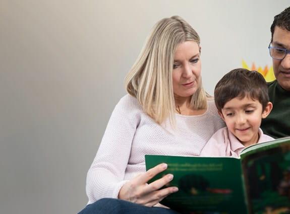 Des parents lisant un livre à leur enfant.