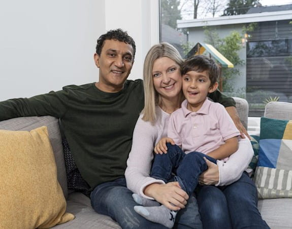 Kathy Andrews sitting on a sofa with her husband and young son