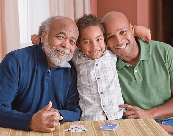 Un jeune garçon étreignant son père et son grand-père.