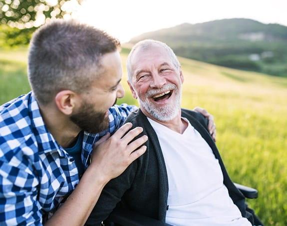 Un homme et son grand-père en train de rire.