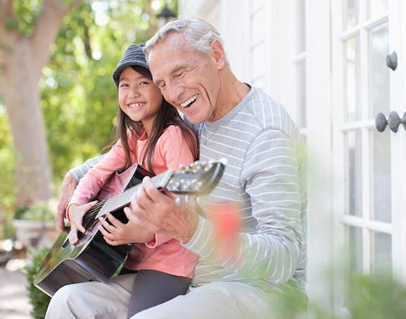 A man plays guitar with his granddaughter.