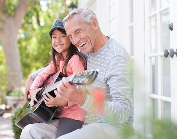 Un homme jouant de la guitare avec sa petite-fille.