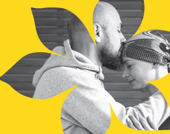 Un homme embrassant le front d'une femme atteinte de cancer.