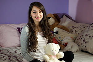 Girl with long brown hair sitting on her bed smiling