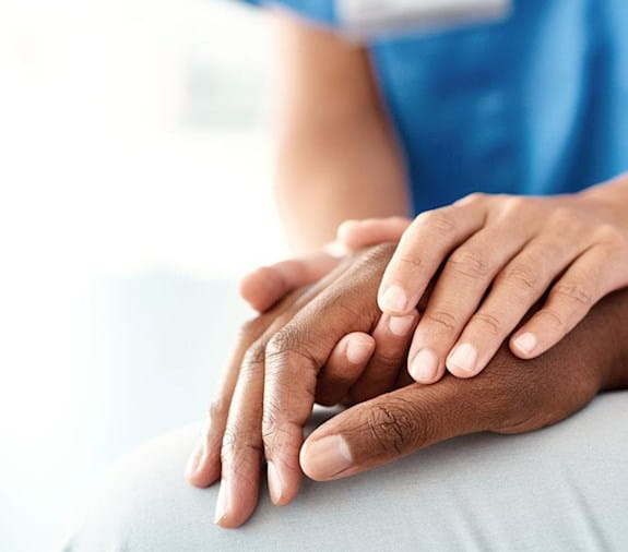 A doctor wraps both their hands around the hand of a patient