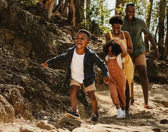 Des enfants devant leurs parents sur un chemin boisé.