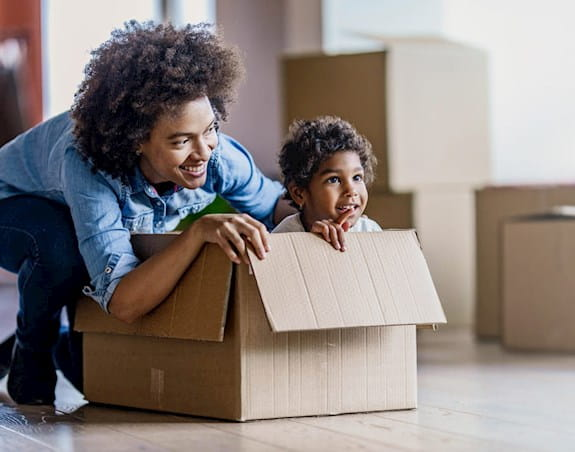 A parent and child playing in a cardboard box on moving day.