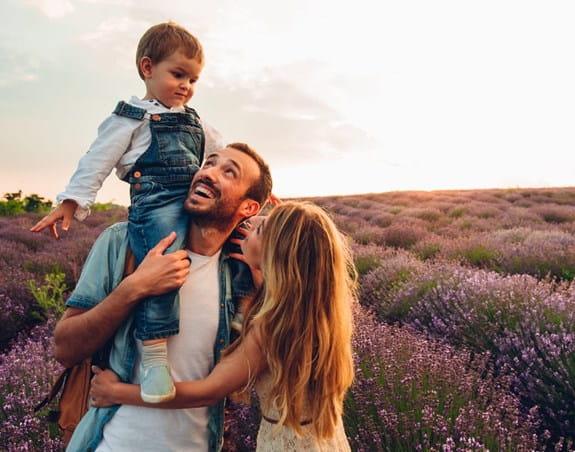 Un homme tenant un enfant en salopette sur ses épaule, avec une femme qui les enlacent dans un champ de lavande.