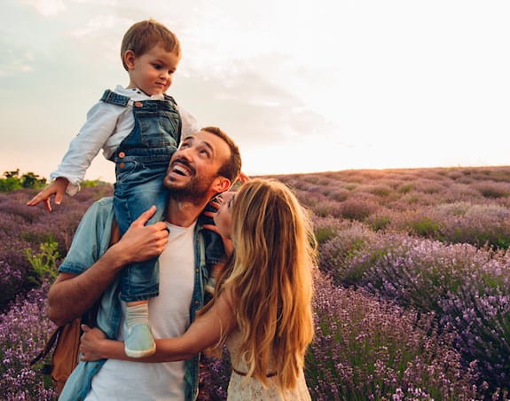 A man with a beard holding a small child in overalls which a woman with long hair embraces him. Lavender field in the background.