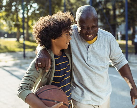 A grandfather and grandson walking together with a basketball.