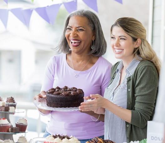 Une femme âgée et une jeune femme tenant un gâteau au chocolat et souriant à une autre femme.