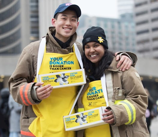 Jeune homme et jeune femme portant des tabliers jaunes de la campagne de la jonquille et tenant des boîtes d'épingles à jonquille à l'hôtel de ville de Toronto.
