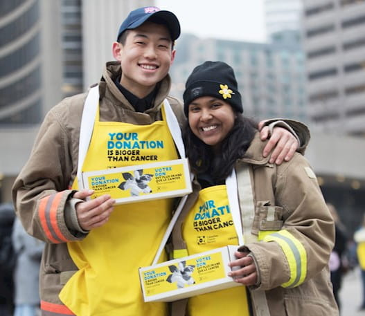 Young man and young woman wearing yellow Daffodil campaign aprons,  holding daffodil pin boxes at City Hall, Toronto