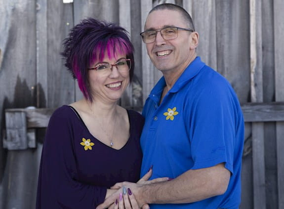 A couple holding each other wearing daffodil pins.