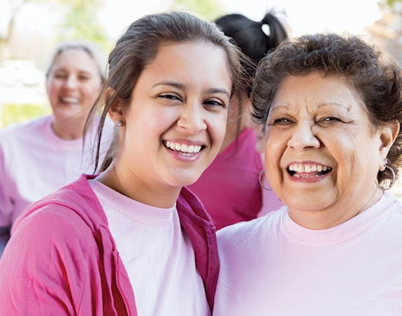 Young woman with dark pink cardigan, light pink shirt beside an older woman. Both women smiling